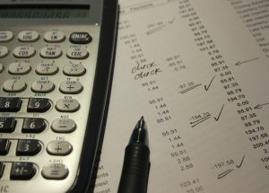 Calculator, pen, and sheet of calculations for refinancing a home